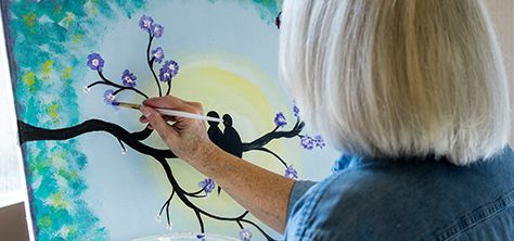 An elderly woman paints purple flowers on a tree