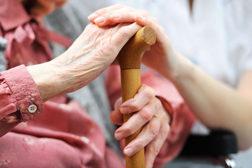 A nurse rests her hand on an elderly woman's hand