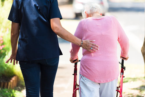 Nurse assists elderly woman walk outdoors