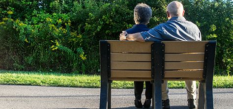 An elderly couple sitting on a bench